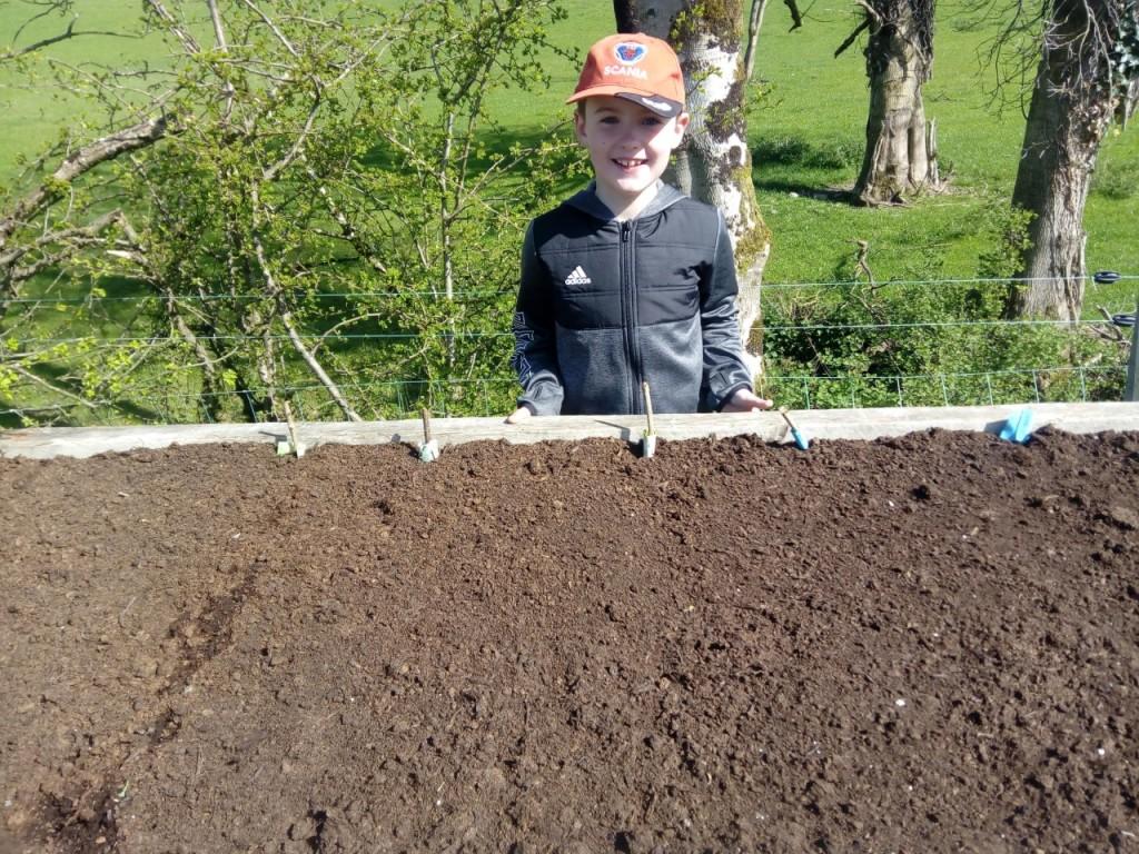 Tomás planting vegtables seeds.